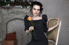 Beautiful brunette with a rose sitting on a chair near fireplace. Young beautiful brunette in black dress with a rose sitting on a chair near the fireplace Royalty Free Stock Photo