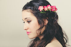 Beautiful brunette with roses in hair Stock Images