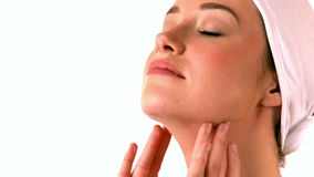 Beautiful brunette rubbing cream on her neck stock video