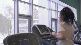 Beautiful brunette runs on treadmill. Beautiful brunette makes sport exercises in the gym. Pretty woman runs on treadmill and trains her legs and body. Young stock footage