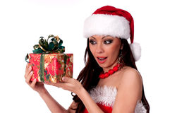 Beautiful brunette Santa Girl  happily looking at Christmas gift Royalty Free Stock Photos