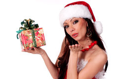 Beautiful brunette Santa Girl holding a gift box and sends a ki Stock Photos