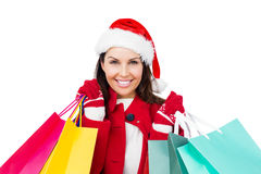 Beautiful brunette with santa hat holding shopping bags Royalty Free Stock Photos