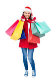 Beautiful brunette with santa hat holding shopping bags Royalty Free Stock Image