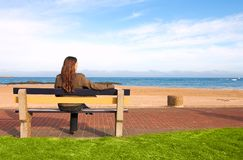 Beautiful brunette at sea. Beautiful brunette woman with long hair on bench on the beach by the sea. Casual clothing Royalty Free Stock Photo