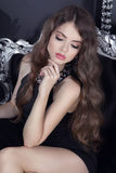 Beautiful brunette sensual girl model with makeup posing on luxury armchair stock photo