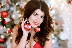 Beautiful brunette sexy Santa Clause in elegant earrings and bra. Fashion portrait of model girl indoors with Christmas tree. Cute woman in lace red lingerie Royalty Free Stock Photography