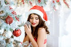 Beautiful brunette Santa Clause in elegant hat and bra. Fashion portrait of model girl indoors with Christmas tree. Cute woman in lace red lingerie with makeup royalty free stock images