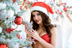 Beautiful brunette sexy Santa Clause in elegant hat and bra. Fashion portrait of model girl indoors with Christmas tree. Cute woman in lace red lingerie with Stock Photo