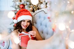 Beautiful brunette sexy Santa Clause in elegant hat and bra. Fashion portrait of model girl indoors with Christmas tree and gifts. Cute woman in lace red Royalty Free Stock Image