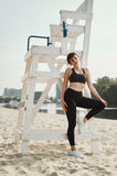 Beautiful brunette with short haircut poses on river beach Royalty Free Stock Photo
