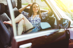 Beautiful brunette in short shorts sitting in car, tinted photo Stock Photo