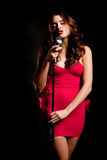Beautiful brunette singer singing with microphone Stock Images