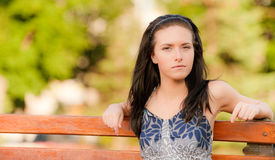 Beautiful brunette sits on bench Stock Photos