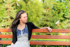 Beautiful brunette sits on bench Royalty Free Stock Photography