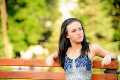 Beautiful brunette sits on bench Royalty Free Stock Image