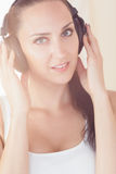 Beautiful brunette sitting on bed listening to music smiling at Stock Photos