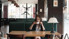 Beautiful brunette sitting in a cafe flirts at the camera. The girl is drinking coffee. stock video footage