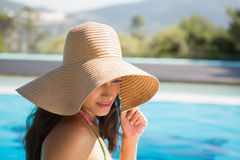 Beautiful brunette sitting by pool wearing straw sunhat Royalty Free Stock Image