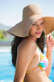 Beautiful brunette sitting by pool wearing straw sunhat Royalty Free Stock Images
