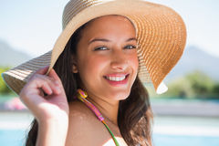 Beautiful brunette sitting by pool wearing straw sunhat Stock Photography