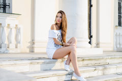 Beautiful brunette sitting stairs. Fashion style concept, tanned long hair, white T-shirt shorts, enjoying a relaxing Royalty Free Stock Photos