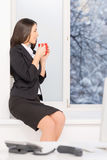 Beautiful brunette sitting on window sill. Royalty Free Stock Photography