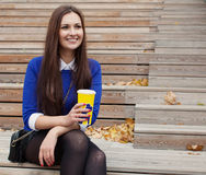 Beautiful brunette sitting on wooden steps with a glass and smiling stock images