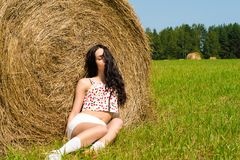 Beautiful brunette sleeping on haystack in summer Royalty Free Stock Images