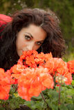 Beautiful brunette is smelling flowers Stock Images