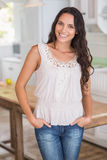 Beautiful brunette smiling at camera with hands in pockets. In the kitchen Royalty Free Stock Image