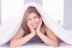 Beautiful brunette smiling at camera under duvet Royalty Free Stock Image
