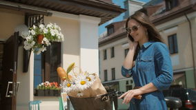 Beautiful brunette smiling girl wearing sunglasses standing near cute building with bike talking on phone. 4K stock video