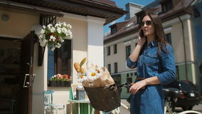 Beautiful brunette smiling girl wearing sunglasses standing near cute building with a bike talking on the phone, slow mo stock video footage