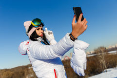 Beautiful brunette snowboarder photographing herselves Stock Photos