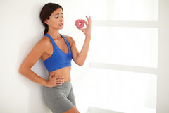 Beautiful brunette in sportswear holding a donut Royalty Free Stock Photos