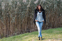 Beautiful brunette standing on a background of reeds. Stock Photo
