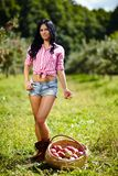 Beautiful brunette standing near a basket of apples Royalty Free Stock Photo