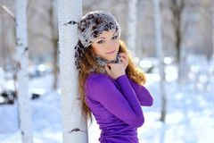 Beautiful brunette standing near birch in winter Stock Photos