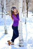 Beautiful brunette standing near birch in winter Stock Image