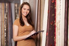 Beautiful brunette standing in store and smiling. Royalty Free Stock Photography