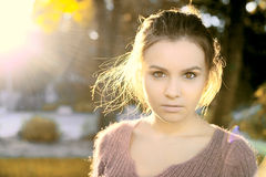 A beautiful brunette stands in autumn sun light Royalty Free Stock Photography