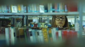 Beautiful brunette student chooses a book in the library. At the university stock video footage