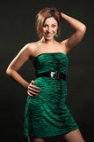Beautiful brunette in the studio. Beautiful brunette in a green evening dress posing in a studio on a black background, fashion photography Stock Photography