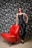 Beautiful brunette in studio with red chair Royalty Free Stock Image