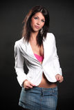 Beautiful brunette in the studio. Beautiful brunette in a white ladies blazer and pink bra and denim skirt posing in a studio, on a black background, fashion and Royalty Free Stock Image