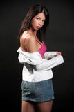 Beautiful brunette in the studio. Beautiful brunette in a white ladies blazer and pink bra and denim skirt posing in a studio, on a black background, fashion and Stock Image