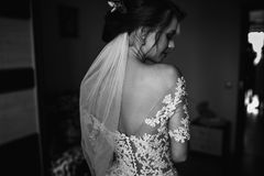 Beautiful brunette stylish bride getting ready in the morning in. Shiny portrait of beautiful bride standing before the window Royalty Free Stock Photography