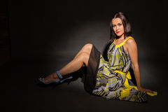 Beautiful brunette in a stylish designer dress on a dark background Royalty Free Stock Images