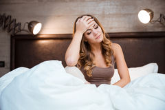 Beautiful brunette suffering from headache in the bedroom Stock Photos